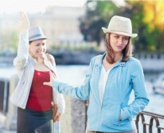 Young beautiful woman having quarrel with her friend in the city outdoor