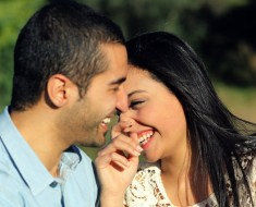 Close up of an arab casual couple flirting and laughing happy in a park
