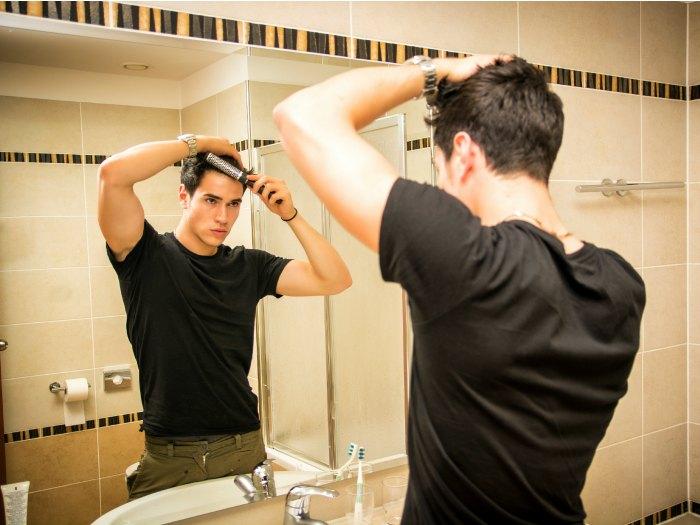 Chico mirandose al espejo  peinandose