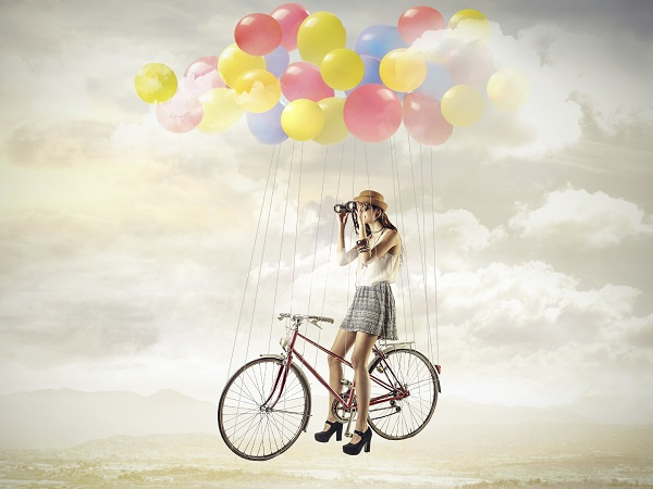 Chica bicicleta globos volar