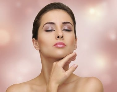 Beautiful woman touching face clean skin on pink background