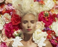 Beautiful blonde young woman lying in flowers