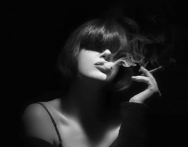 Young woman smoking a cigarette. Monochrome portrait