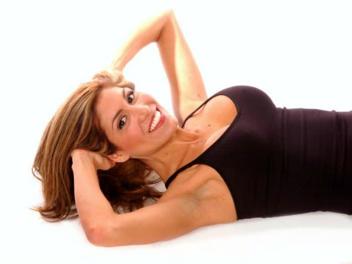 Mujer tumbada haciendo ejercicios para el pecho