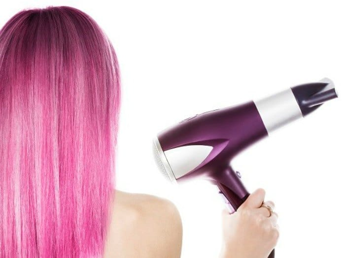 Chica secándose el cabello con un secador