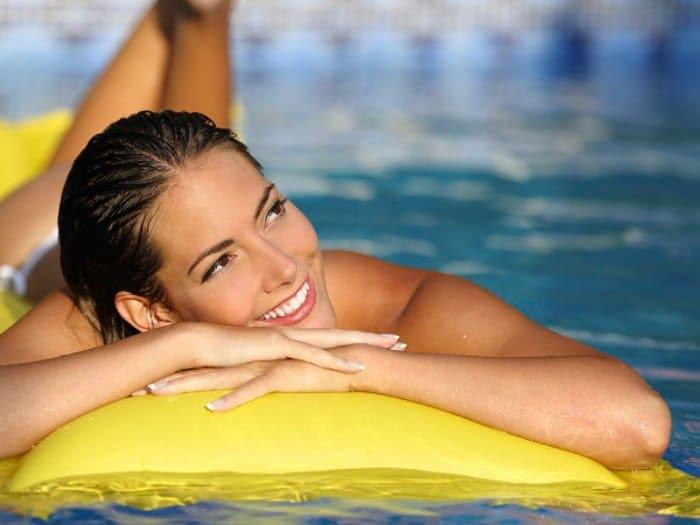 Chica tomando el sol en la piscina