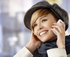 Outdoor portrait of young woman talking on mobile phone in winter sunshine