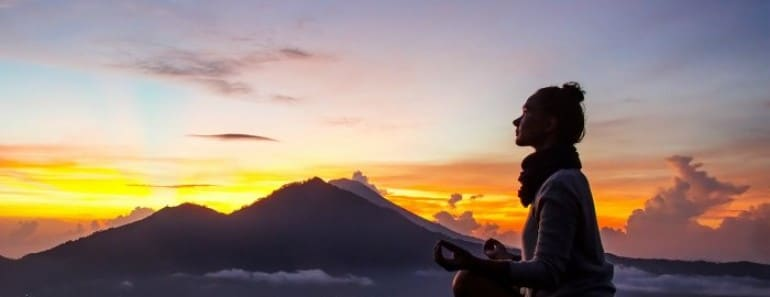 Silhouette of a girl that does yoga and meditation in the mountains at dawn. Stock image.