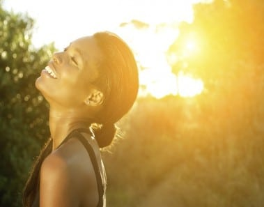 Close up portrait of a smiling african american sports woman standing outdoors