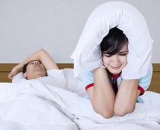 Young couple in bed. Woman trying to sleep while a man is snoring