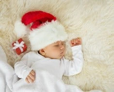 Baby sleeping with christmas hat on and gift box