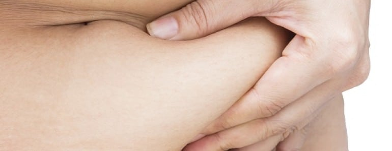 Overweight woman hand holding or pinching fat body belly paunch