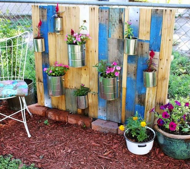 latas de pintura y conserva fijadas a una valla hecha con tablones de madera