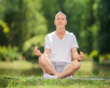 Calm senior man meditating in a park seated on a blanket in a field