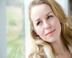 Close up portrait of a young woman gazing out window