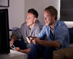 Two Young Men Playing Video Game At Home