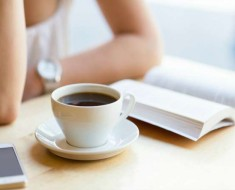 Girl reading a book and drinking coffee at a cafe