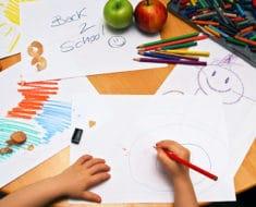 Little hands drawing between school supplies and apples