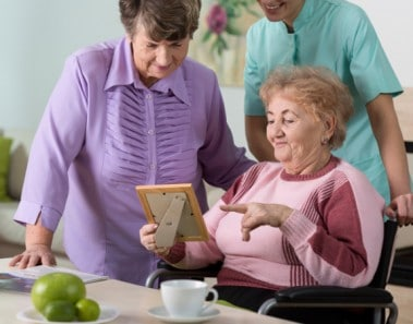 Two aged women and young therapist looking at picture