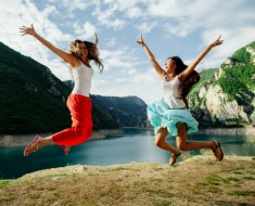 two long hair girls happy jump in mountains with exciting view of Montenegro