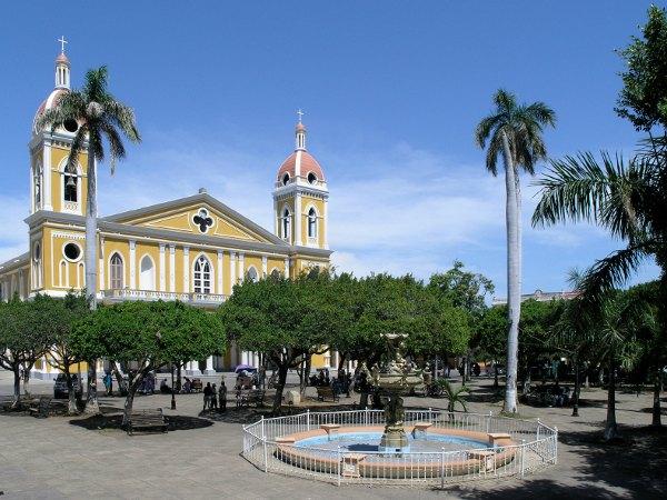 Fuente en una plaza arbolada con iglesia al fondo en Granada, Nicaragua