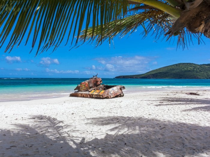 Rusted old tank covered in graffiti on famous Flamenco Beach framed by palm tree on beautiful Isla Culebra, Puerto Rico