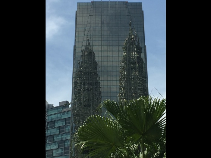 Viajar a Malasia: Reflejo Torres Petronas en edificio cristal, Kuala Lumpur